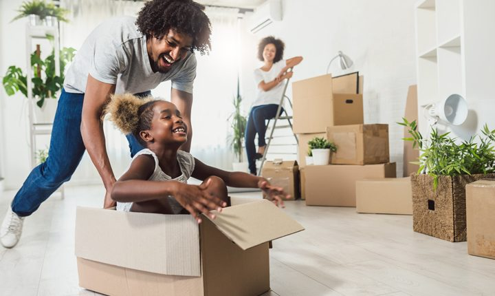 African American father pushing daughter in box while moving into a house